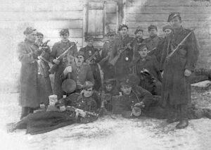 """Druga część oddziału, połowa lutego 1946 roku Od lewej stoją: """"HARDY"""", NN, """"SKIBA"""", """"CYGANEK"""", """"WILK"""", """"ROLA"""", """"TOKS"""", """"PAX"""", """"ŻABKA"""", """"ZBYCH"""" Od lewej klęczą: NN, """"KRUK"""", od lewej leżą: """"KALO"""", """"WICHER"""", """"BURZA""""."""