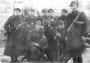 """Pierwsza część oddziału, połowa lutego 1946 roku: Od lewej stoją: NN, prawdopodobnie """"CICHY"""", """"DZIK"""", """"WILCZEK"""", NN, """"ZBYCH"""". Od lewej klęczną: """"GROM"""", """"GRAD"""""""